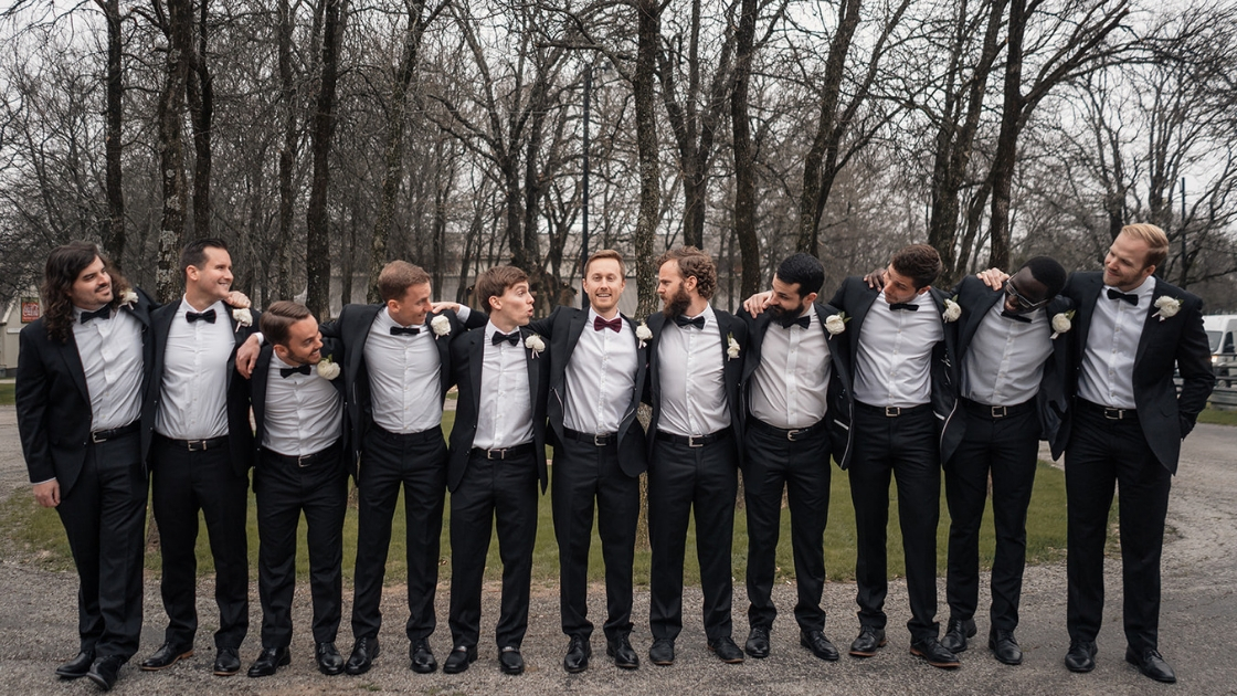 10 Groomsmen in black tuxes and bow ties white skirts smile and pose on friend's wedding day trees in background