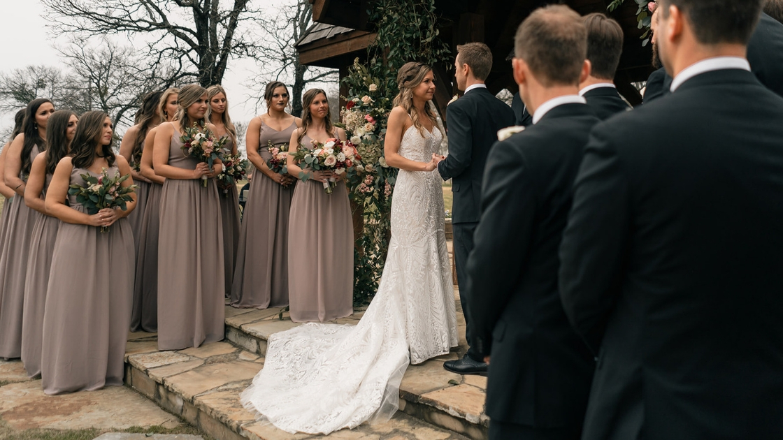 11 bridesmaids in pink taupe chiffon dresses holding pink and burgundy flowers smile and watch bride in revelry decklyn wedding gown get married