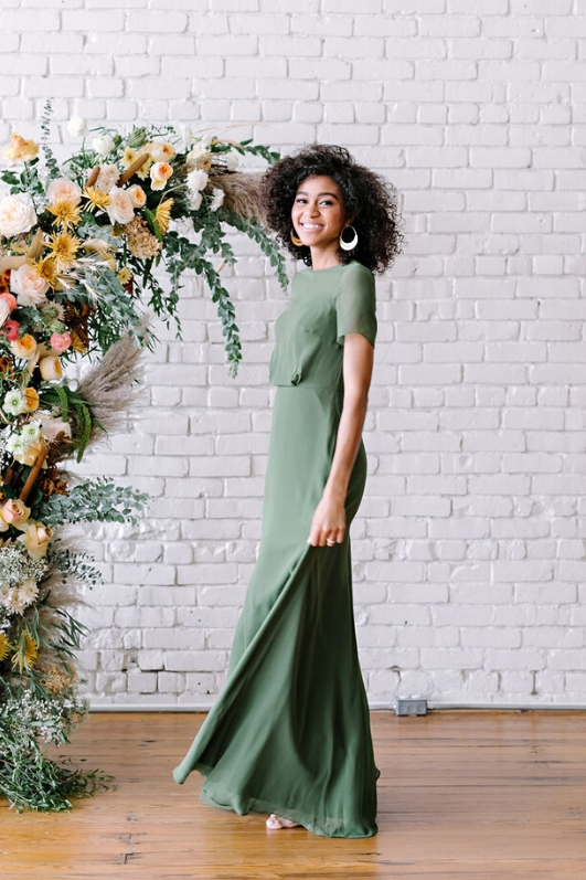 Becca chiffon bridesmaid gown in olive color bride in front of floral arrangement at one eleven east in austin texas