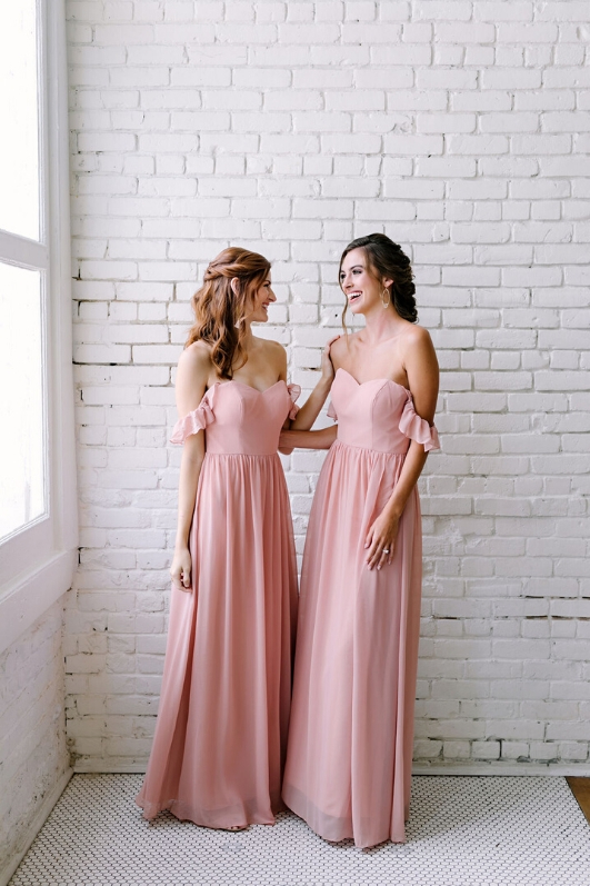 two bridesmaids in soft pink revelry chiffon bridesmaid dresses with ruffle sleeves