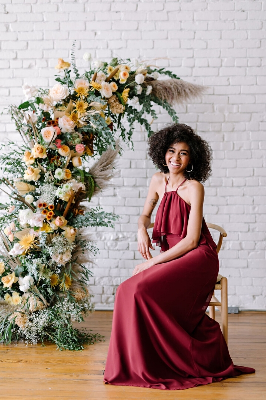 bridesmaid in chiffon burgundy gown smiling and sitting in front of floral arrangement