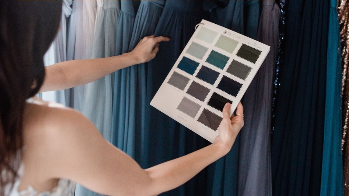 Two brides are better than 1 bride in blue luna revelry bridal gown holding up swatches in different blue and green tulle colors
