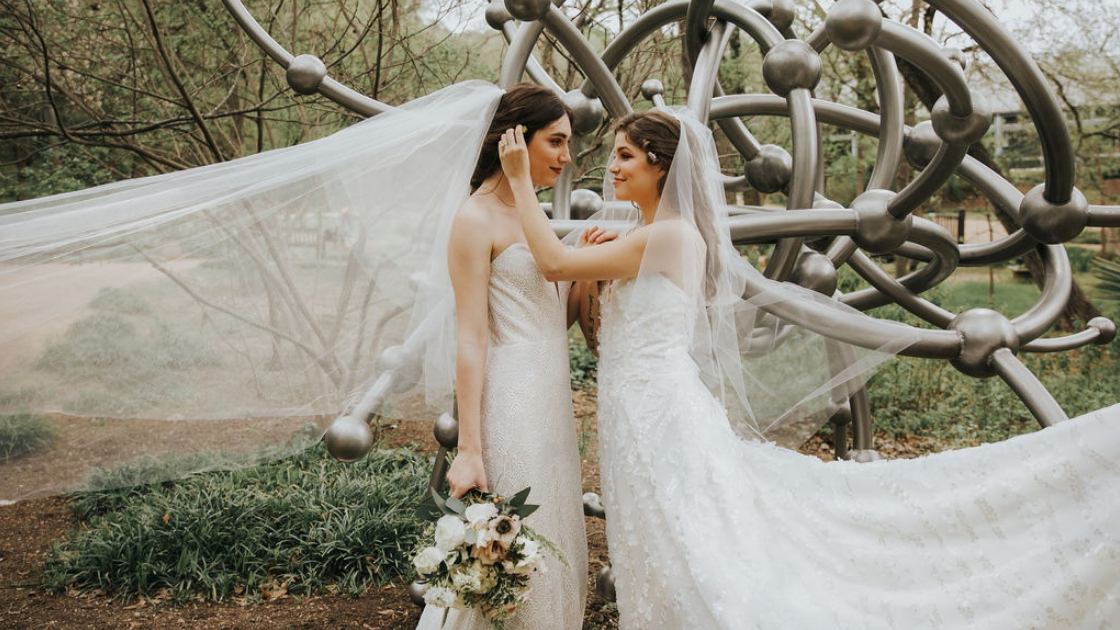Two brides are better than 1 brides in revelry gowns veils wedding dresses holding flowers florals tucking hair behind ear