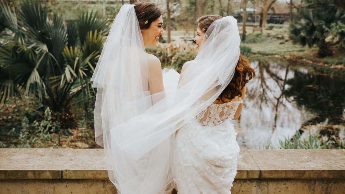 Two brides are better than 1 facing back in revelry form fitting wedding dresses laughing and posing on wedding day in veils