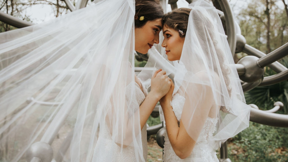 Two brides are better than 1 brides holding hands and gazing into each other's eyes on wedding day holding hands