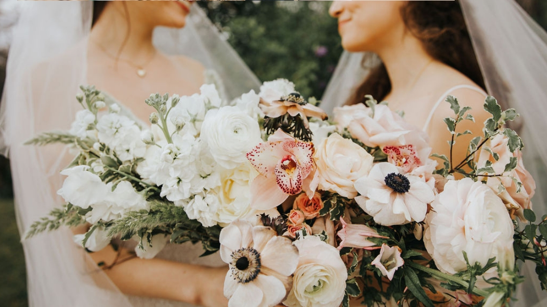 Two brides are better than 1 brides smiling looking at each other with love holding florals