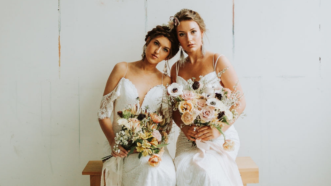 Two brides are better than 1 brides in wedding dresses wearing revelry bridal gowns sitting holding bouquets on wedding day