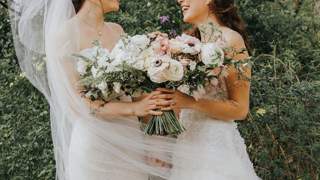 Two brides are better than 1 flowers holding brides on wedding day laughing and posing and looking at each on love