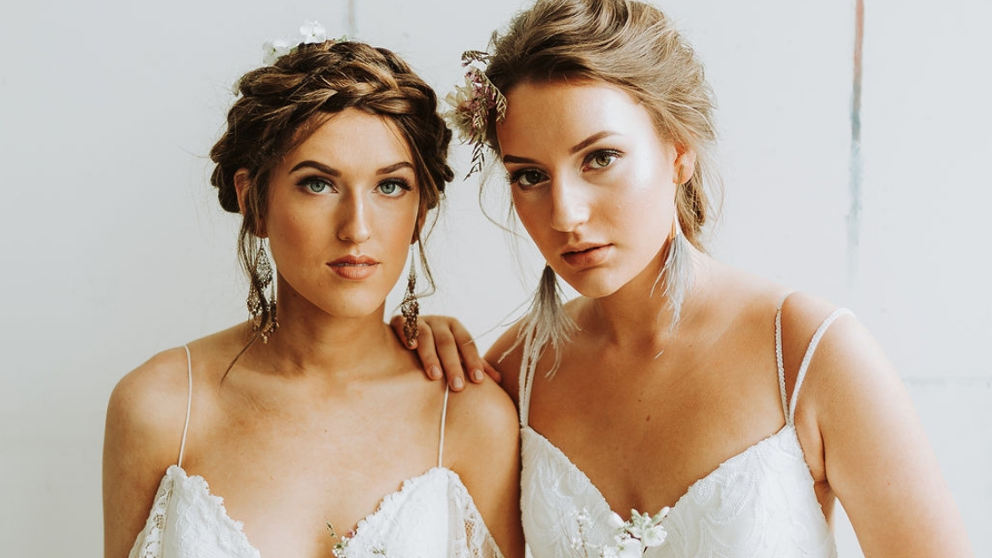Two brides are better than 1 headshot of two brides in revelry bridal gowns posing on wedding day