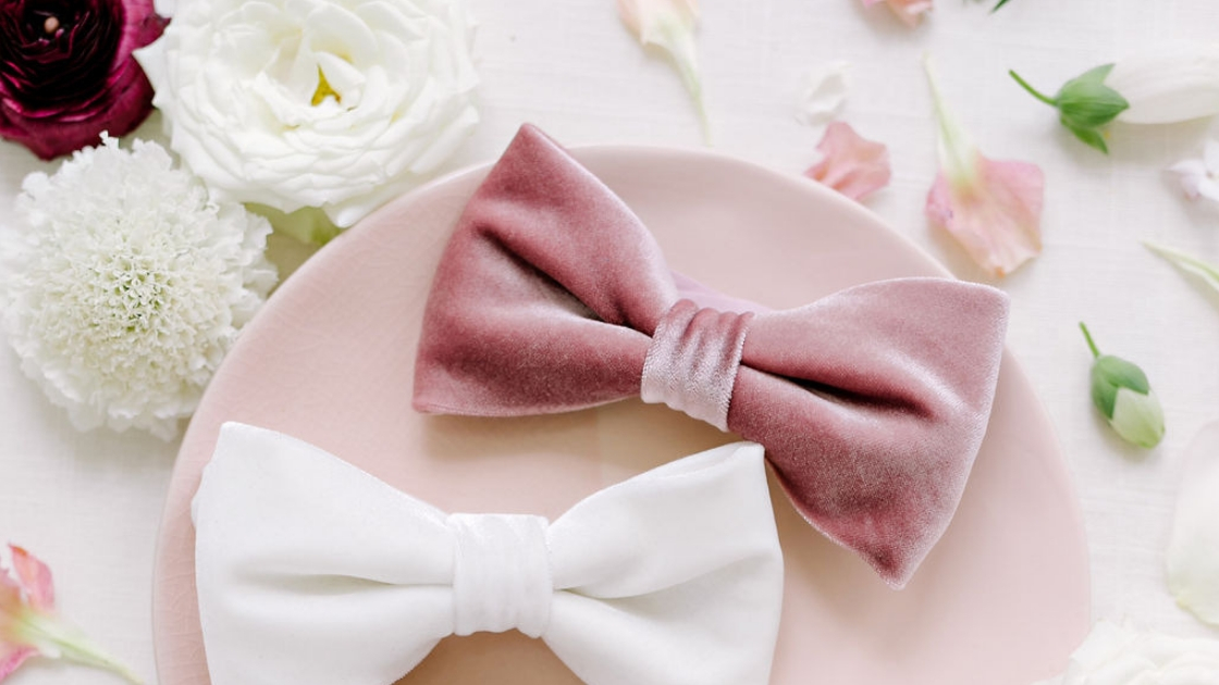Two brides are better than 1 two velvet bow ties in white and pink colors flay lay with pink and white flowers