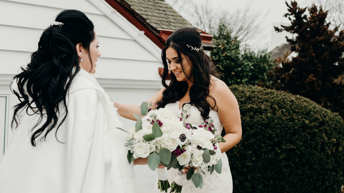 2 brides on wedding day in wedding dresses smiling and posing holding white and purple florals first look brunette brides looking and laughing at each other wedding day