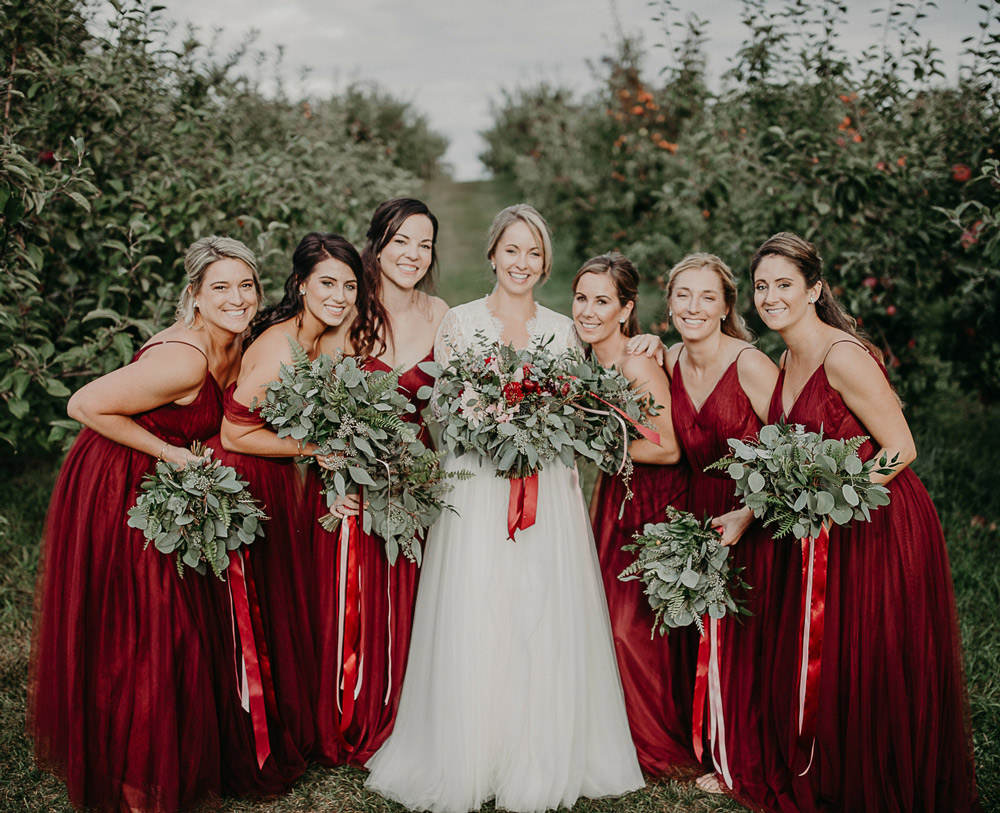 Autumn love romance in an east coast apple orchard revelry bridesmaids stand with bride in apple orchard wearing revelry cabernet tulle bridesmaid dresses in rosalie ombrellifo Images