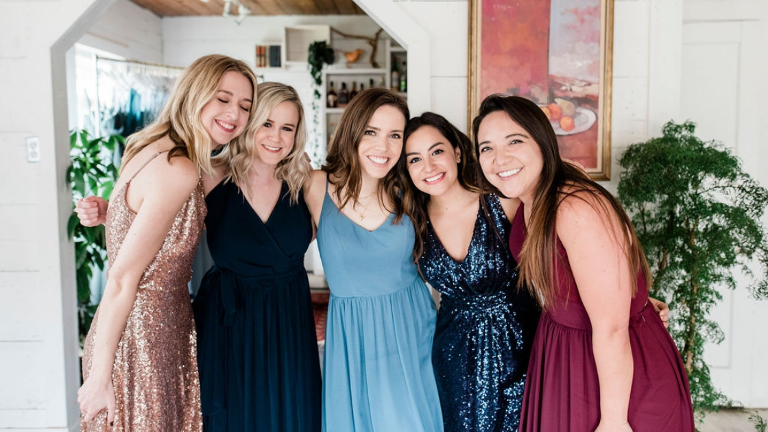 5 bridesmaids in revelry dresses hazel sequin bijou navy burgundy navy and light blue gowns smile and pose at blg try on party