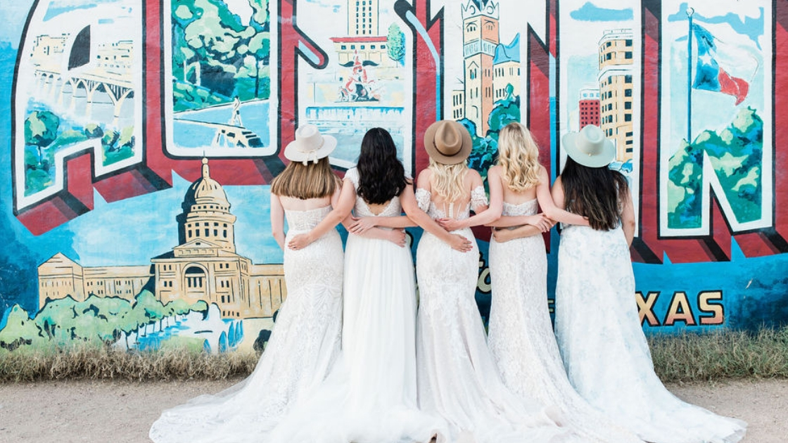 5 girls in mid twenties facing back wearing wedding dresses posing in austin texas in front of greetings from texas mural wearing cowboy hats