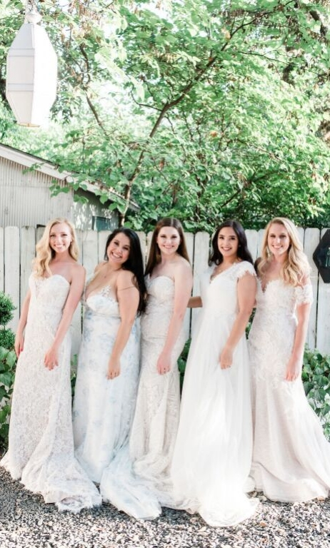 5 revelry finally the brides smiling and posing in bridal gowns facing to the side in yard with green trees lamp hanging