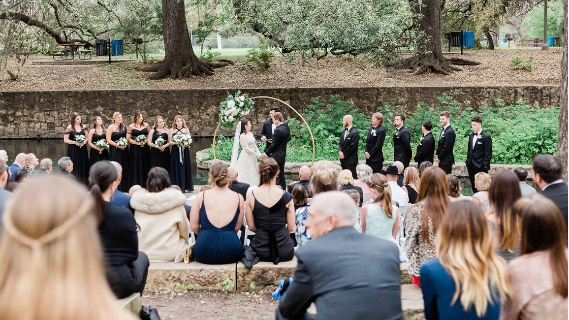 6 bridesmaids and 6 groomsmen standing at alter at outdoor wedding ceremony in park with circle alter greenery white roses bouquet