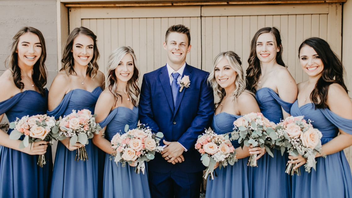 6 bridesmaids in blue revelry chiffon kennedy wedding dresses holding pink flowers smile and pose next to groom in navy suit on wedding day
