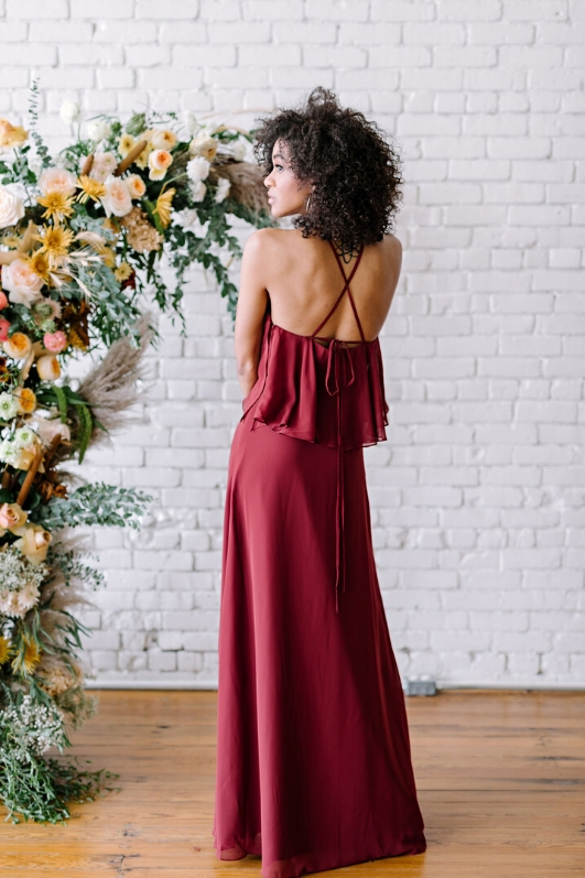 back view of revelry chiffon gown with crisscross back in burgundy color in front of floral setup