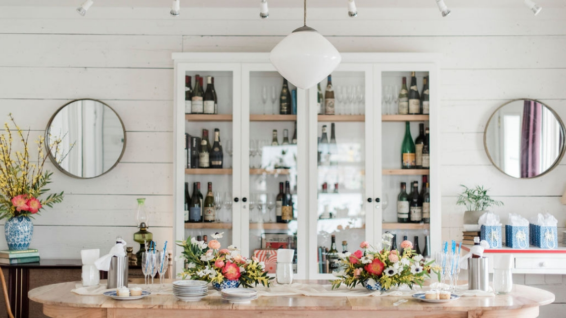 Austin Texas venue space farm table white background bar spirits florals cupcakes and champagne glasses