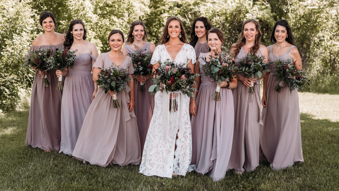 Bridesmaids in revelry chiffon mauve dresses kennedy wrap dresses separate and boho bride in the center posing on wedding day