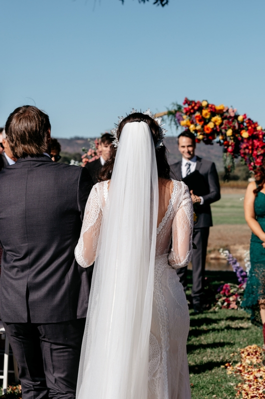Back view of bride walking down aisle with fther on wedding day toward groom cathedrial length veil and flower covered alter with pink yellow and purple