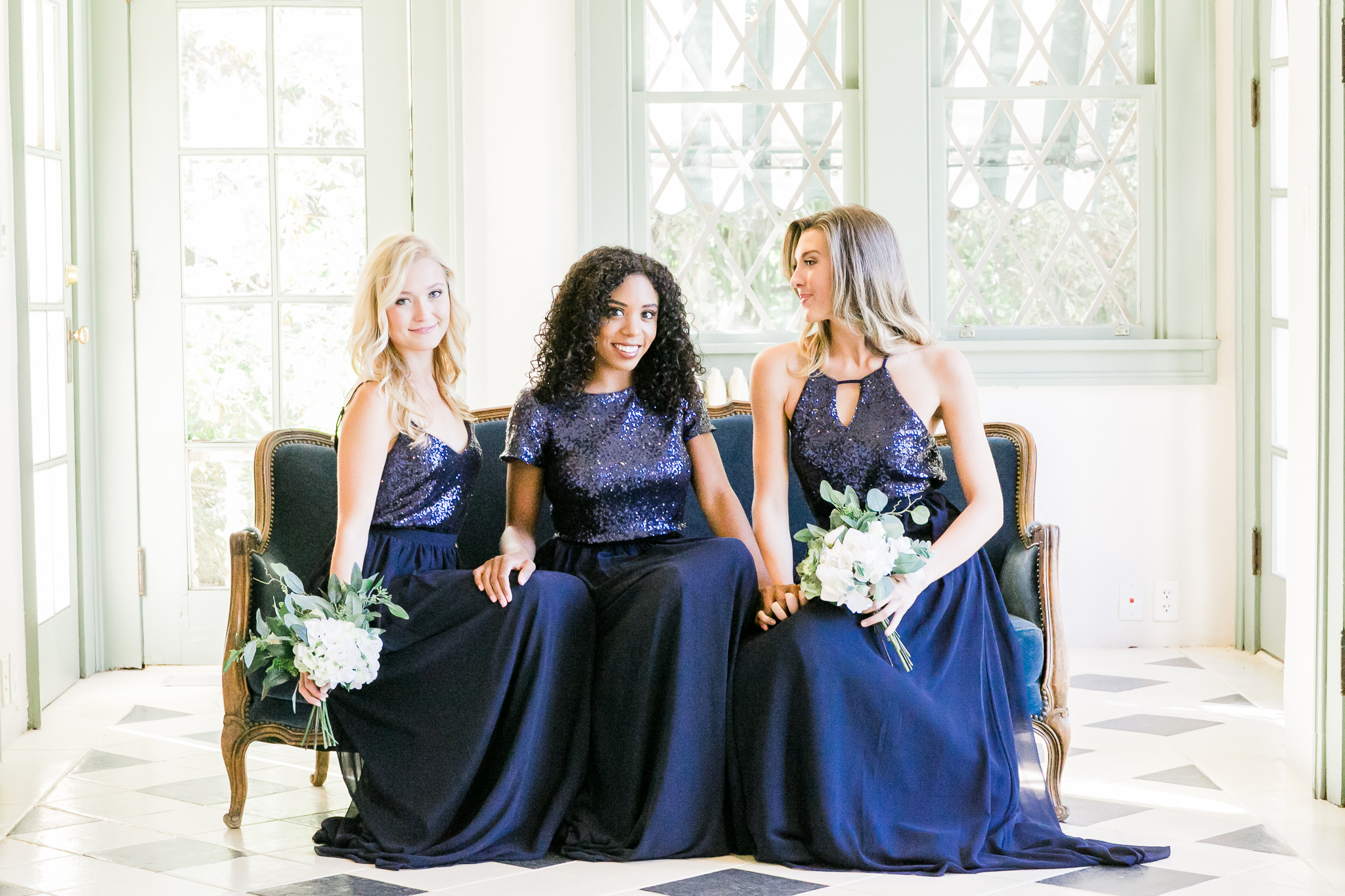 Bridesmaids in Navy sequin tops and chiffon navy skirts. Girls sit together inside beautiful wedding art venue while sitting on a glamorous couch..