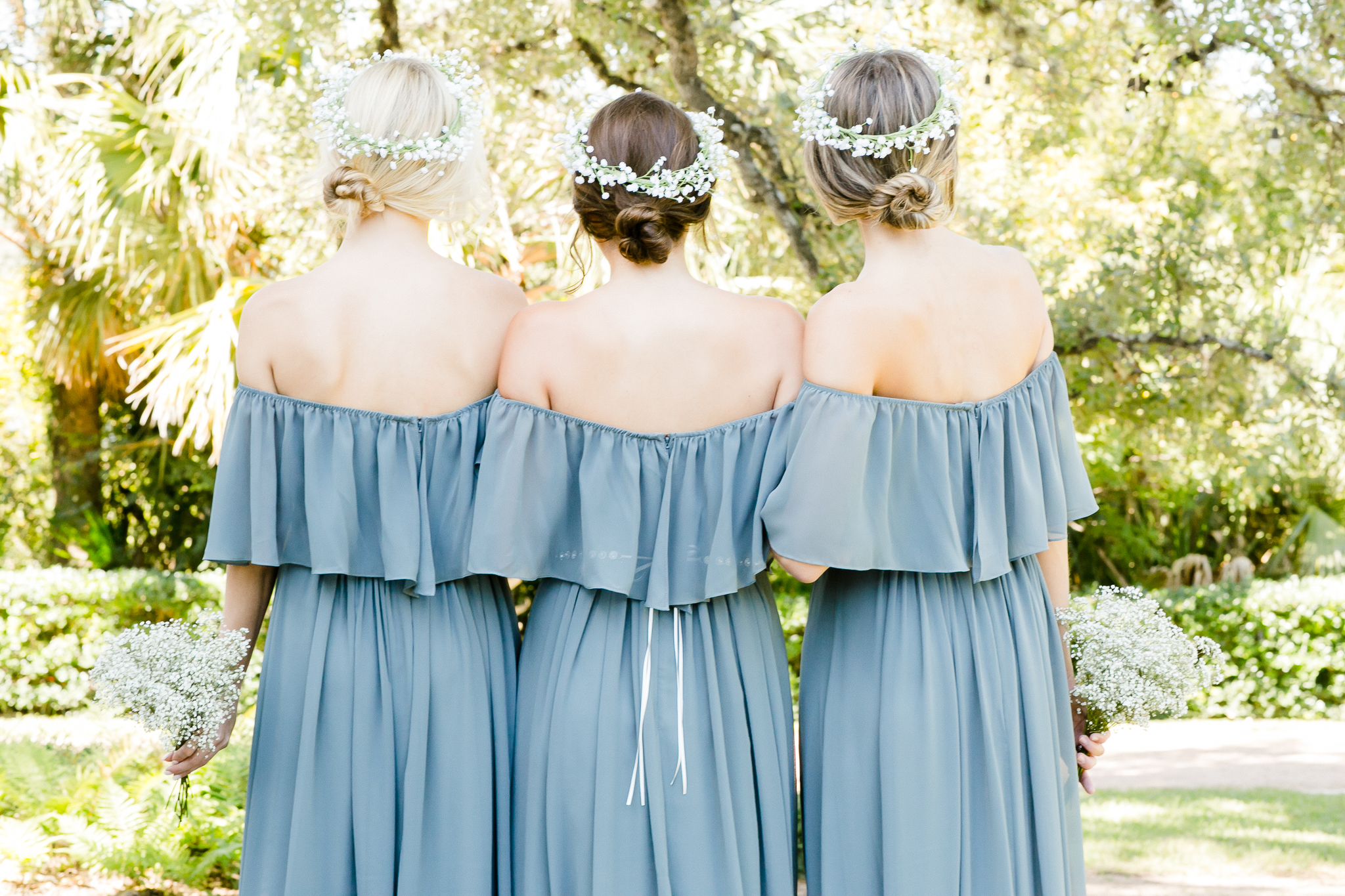 three bridesmaids pose together looking in to the distance highlighting the off the shoulder boho ruffle dress paired with bright white flower crowns.