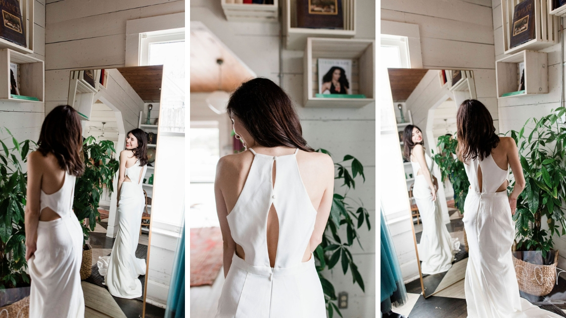 Beautiful brunette bride wearing white cut out crepe wedding dress post in front of mirror ad austin try-on party key hole back