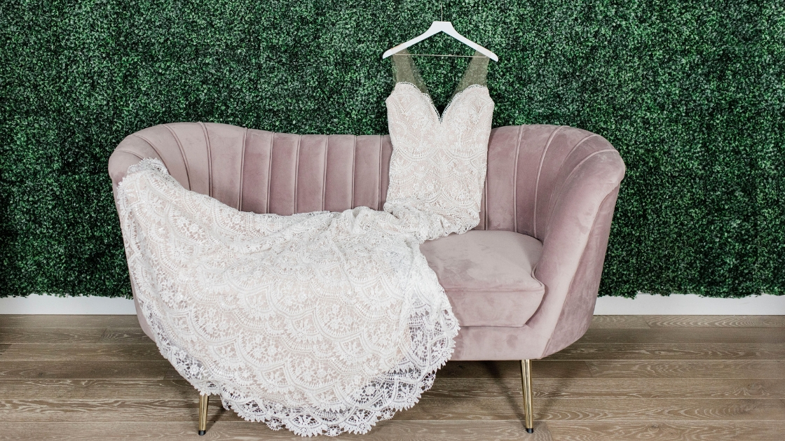 Beautiful lace wedding dress detail on couch in mauve against green wall pretty