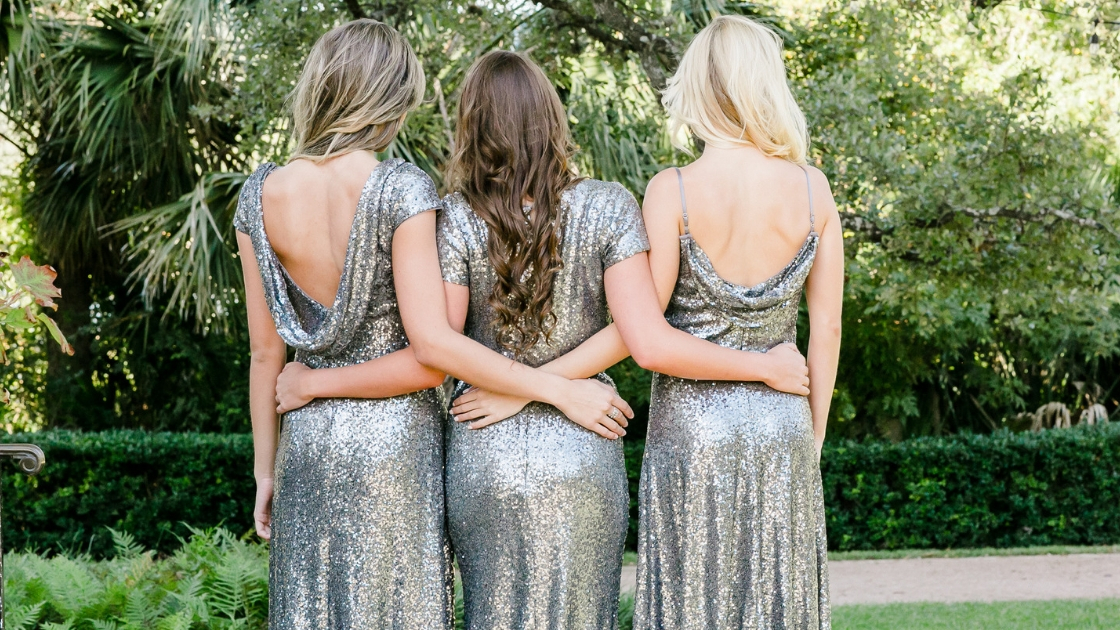 best friends in silver grey sequin dresses with low backs hug and cuddle over the holidays