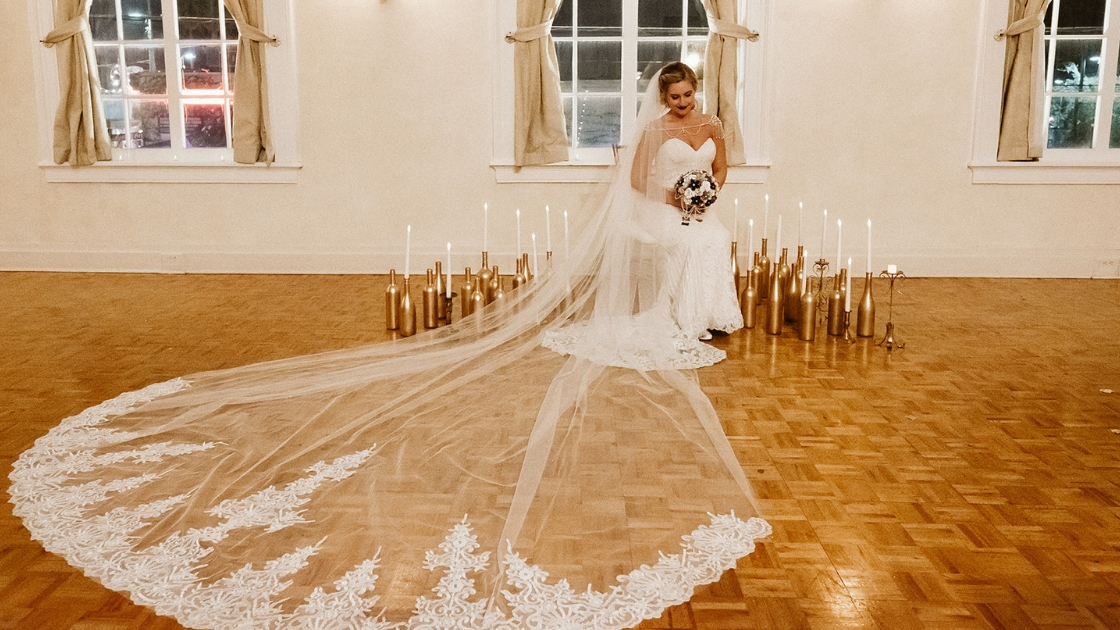 blonde bride with ling train poses with gold wine bottles all around glowing and looking beautiful