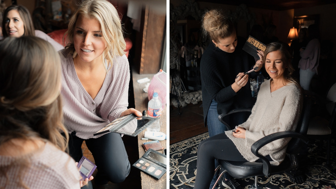 blonde bridesmaid in button down thermal pink shirt puts makeup on friend on weddign day bride in rolling chair gets makeup done on wedding day