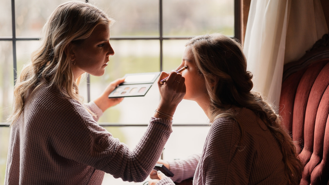 Blonde bridesmaid in thermal long sleeve mauve short puts eyeshadow on bridesmaid in front of window on best friend's wedding day