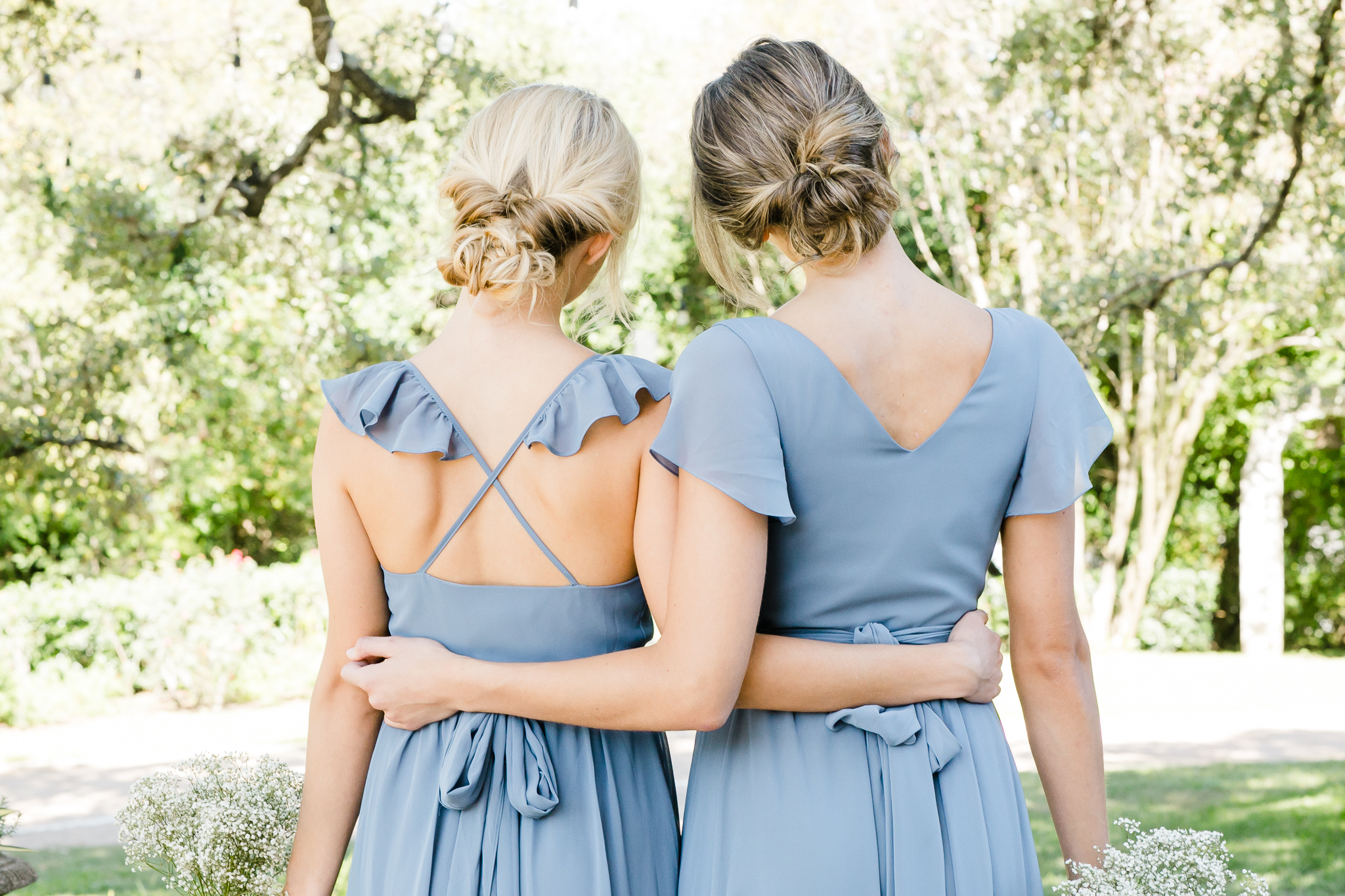 Dusty blue chiffon wrap dresses with sleeves, and ruffles. These bridesmaids are hugging and showing off the back details of these modern bridesmaids styles.