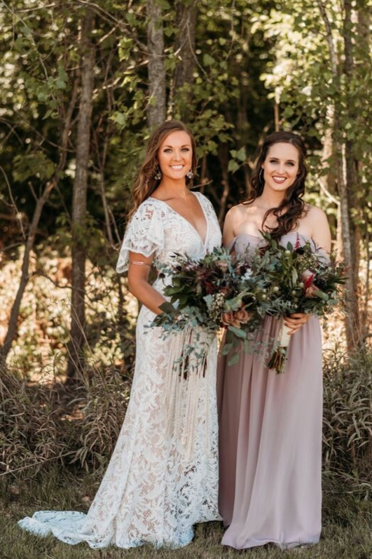 Boho bride in lace bridal gown with sleeves bridesmaid in revelry kennedy chiffon off the shoulder gown in melted mauve holding greenery flower bouquet