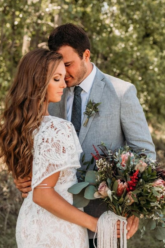 Boho bride in lace wedding dress poses as model on wedding day with groom grey suite bouquet