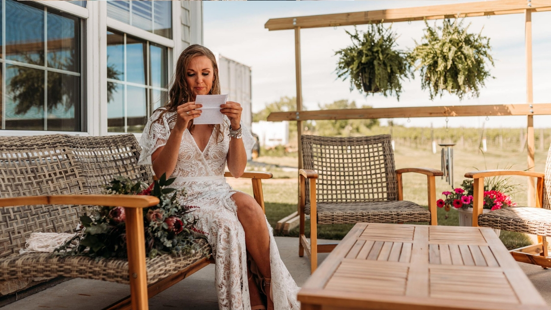 Boho bride reading note from groom on wedding day before ceremony in lace bridal gown wedding dress brown hair bride sitting outside before ceremony
