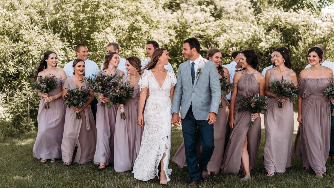 Boho bride with lace bridal gown with slit up the side walks wirth bridesmaids and wedding party on wedding day holding hands with groom and holding florals of greenery and flowers