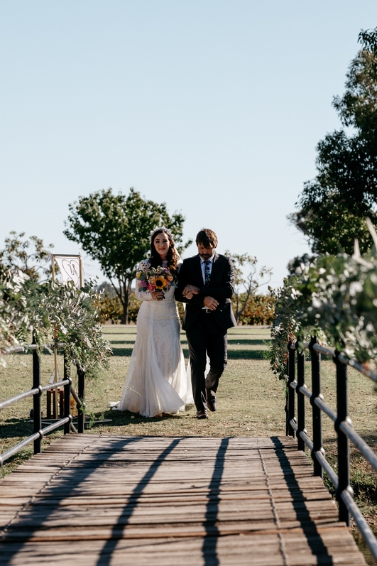 Boho brunette bride in crown walking down bridge aisle with dad on wedding day greenery and trees all around