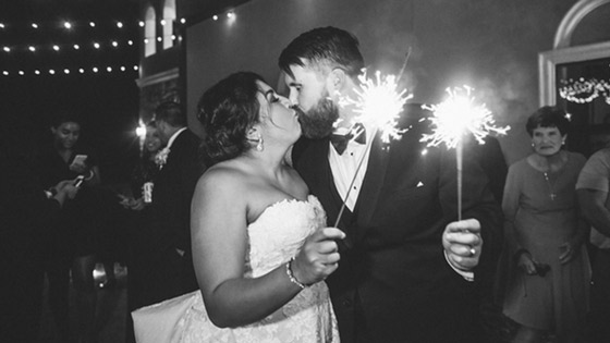 bride and groom kissing with sparklers as they exit the ceremony.