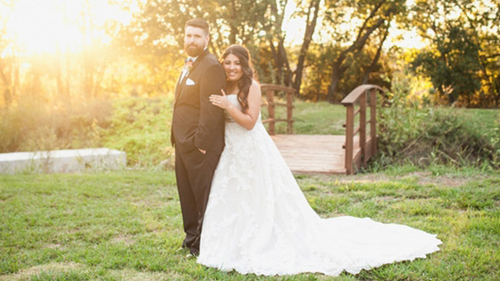 bride and groom pose next to bridge in texas sunset wedding portrait