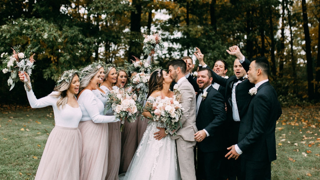 Bridal party outside on beautiful fall october day smile and cheers as bride and groom kiss on wedding day marriage bouquets in the air and happiuness all around