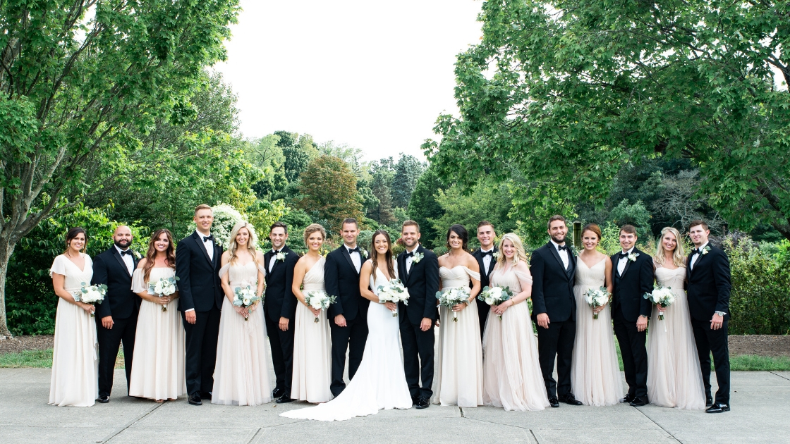 Bridal party posing on wedding day in front of trees and greenery eight bridesmaids and eight groomsment holding bouquet posing formal photos before wedding