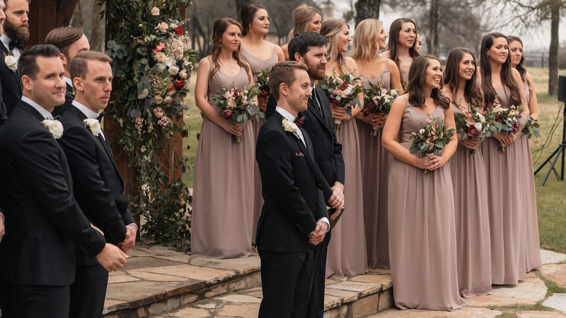 Bridal party with 11 bridesmaids and 10 groomsmen stand outside at venue holding flowers waiting for bride to walk down aisle