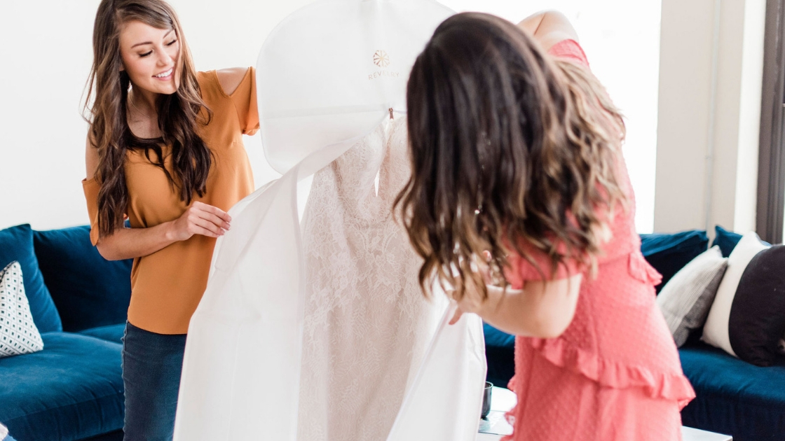 Bride and bridesmaid putting back revelry bridal gown in garmet bag after try on party to send back after three days with the sample to fall in love with the styles