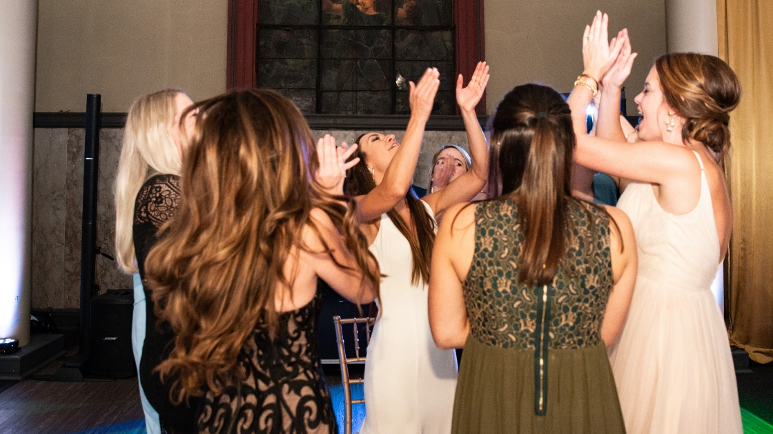 Bride and bridesmaids clapping and dancing at wedding reception laughter love claps packed dance floor revelry wedding