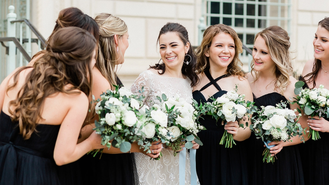 Bride and bridesmaids in tulle and chiffon black tie revelry dresses hair half up half down white roses greenery bouquet lace wedding dress