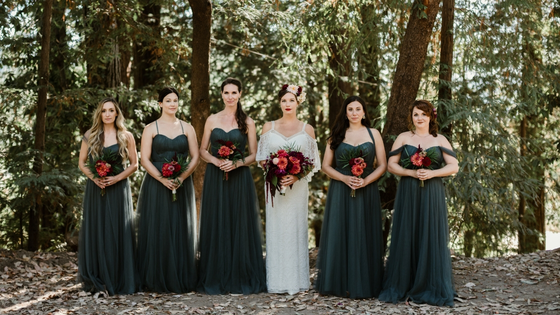 Bride and five bridesmaids hold pink and orange flowers and rosalie green dresses in wooded forest location