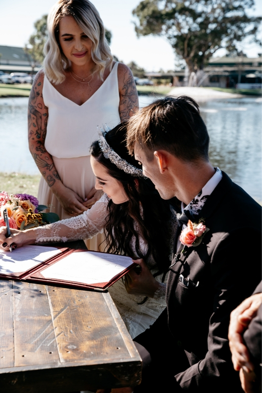 Bride and groom boho style signing wedding certificate on wedding day with sister and maid of honor in revelry watching and signing
