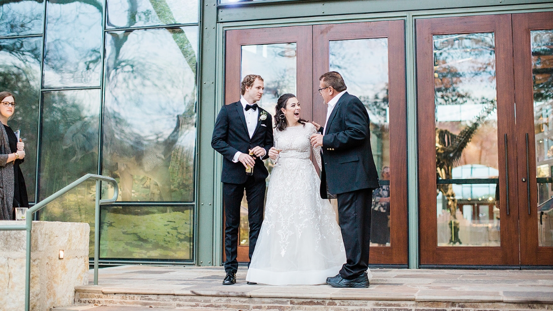 Bride and groom enter reception after cocktail hour at wedding father giving toast standing on patio